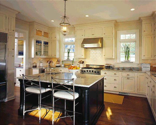old world kitchen with black island, white kitchen cabinets and neutral granite - via Atticmag