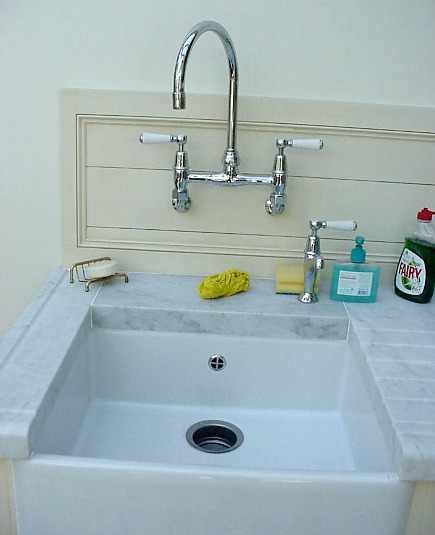 small farm sink used in a pantry with wall-mounted faucet and cold water tap