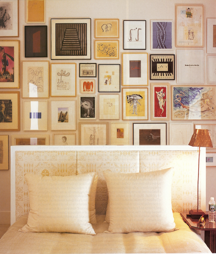 picture wall ideas - frames of different size and color on a picture wall of art hung behind a bed - Town & Country