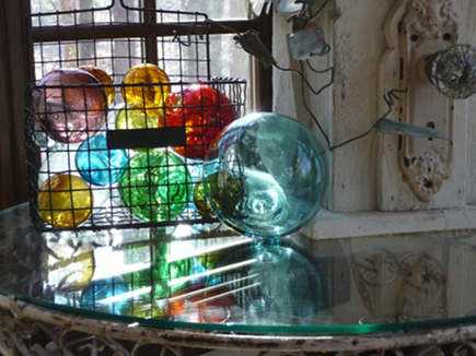 wire basket holding a collection of colorful Japanese glass fishing floats - Gems of the Ocean via Atticmag