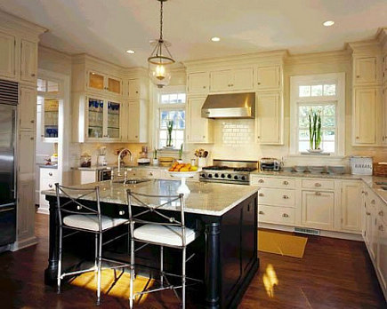 traditional style kitchen with white cabinets, black island and neutral granite