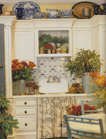 Charlotte Moss cream cabinets with delft tile backsplash and toile skirted sink