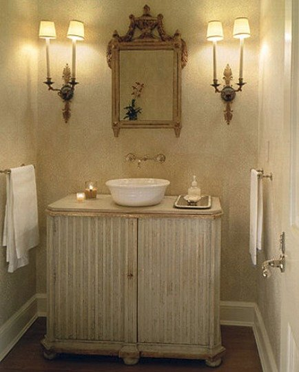 monochromatic powder room with furniture sink cabinet, sconces and mirror