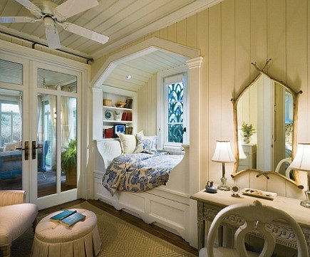 cozy custom bed alcove with wood ceiling and book shelves