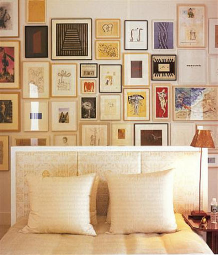 picture wall of art hung behind a bed