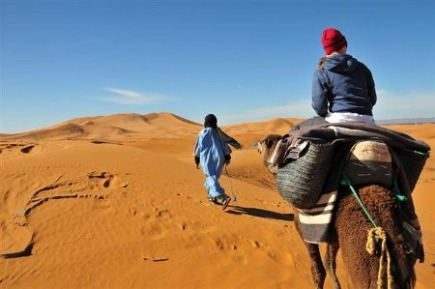 rugs in morocco -- traveling by camel on the dunes of Erg Chebbi with a saddle made of rugs - Atticmag