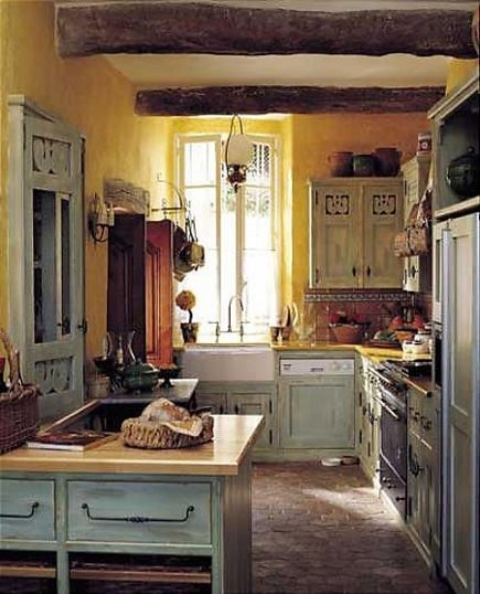 French provincial kitchen with yellow stucco walls and pale blue rooster motif cabinets
