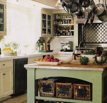 sage green island kitchen with white cabinets and quilted aluminum range guard