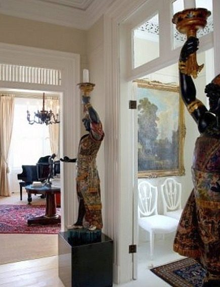 stone mansion - a pair of polychrome blackamoor torcheres in the hallway of a historic stone mansion outside Toronto - mauspark via atticmag