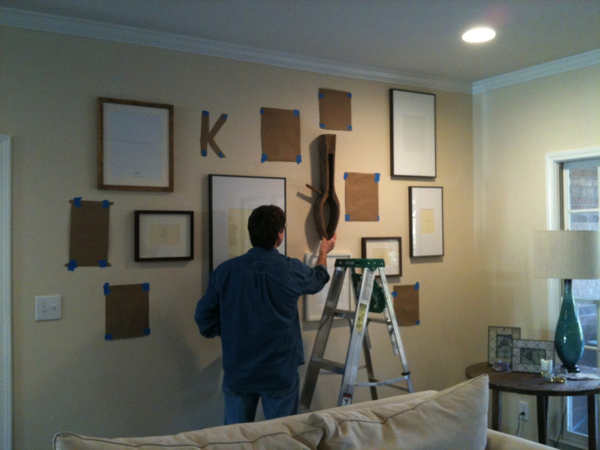 informal picture wall - Mr. Shops installing pictures and objects over the template - Atticmag