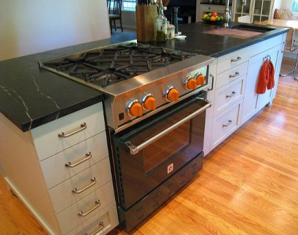 dark green Blue Star range with orange knobs in black and white kitchen island
