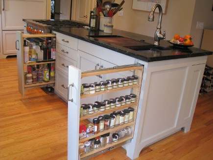 pull-oout condiment and spice storage in the island of the renovated black and white kitchen