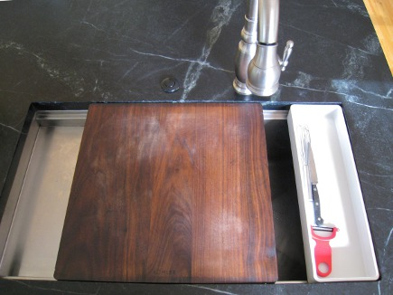 serious cook's kitchen - Kohler Stages sink with cutting board and utensil tray inset in M. Teixiera soapstone counter - Atticmag