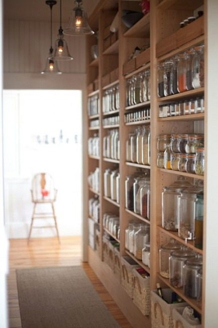 open pantry shelves lining hallway with glass storage containers