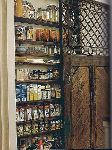 pantry ideas - narrow storage pantry covered by sliding interior wood and latticework barn door - via Atticmag