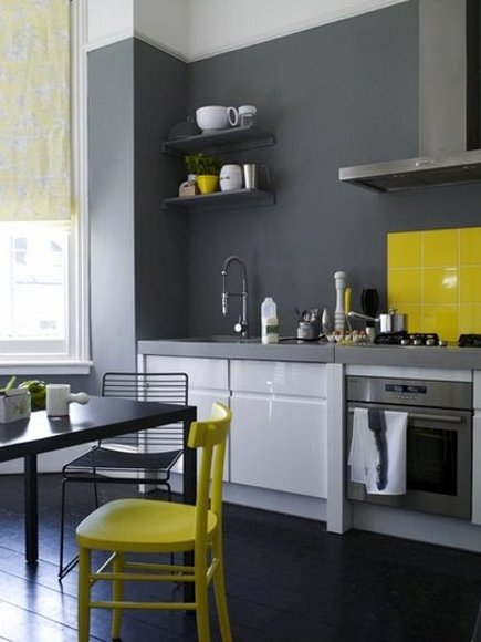 dark gray and white kitchen with yellow range guard and chair