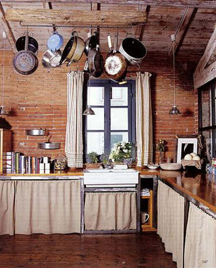 Italian country kitchen with linen skirts on cabinets - WOI via Atticmag