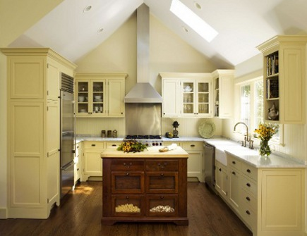 pale yellow kitchen with vaulted ceiling and antique island