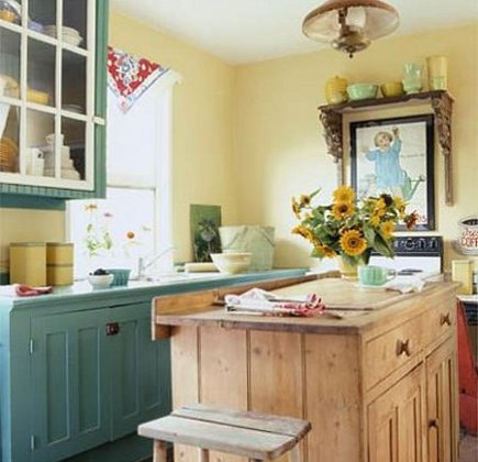country cottage kitchen with yellow walls, a pine island and teal cabinets.- via Atticmag
