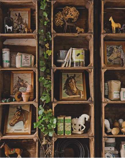 vintage wooden crates used as wall shelves for displaying a horse collection