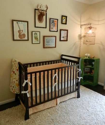 eclectic gender neutral nursery with dark stain wood sleigh style adjustable crib and custom crib bedding