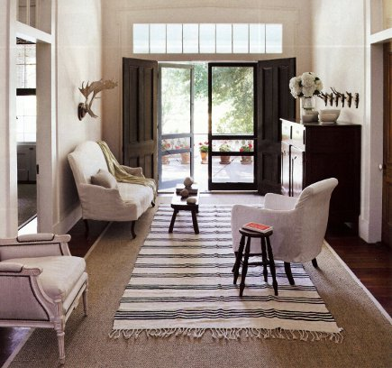 black and white striped dhurrie rug over sisal in a hallway