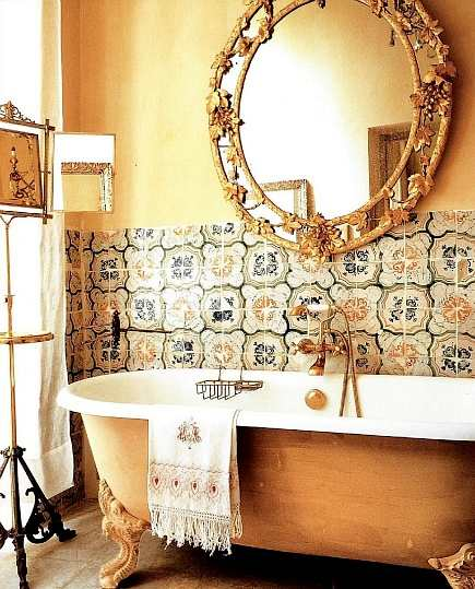 painted clawfoot tub bathroom with intricate mirror and tile wainscot