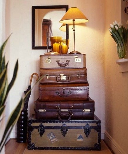 a hallway table made from a stack of suitcases