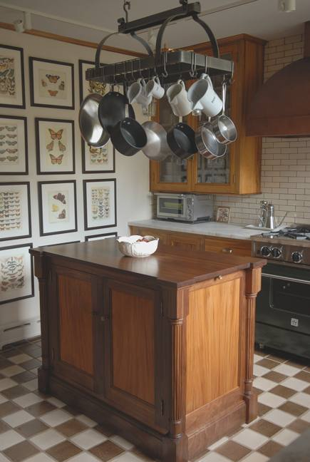 gumwood and walnut island in vintage gumwood cabinet kitchen with copper hood and Enclume potrack in a 1927 home - Atticmag