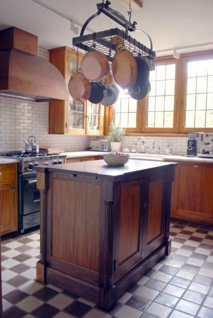 gumwood and walnut island in vintage gumwood cabinet kitchen with Seneca Tile checkerboard floor and replaced windows - Atticmag