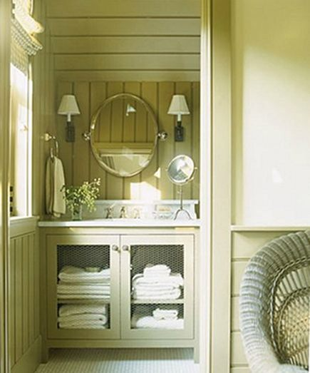 chicken wire inserts in a khaki-green lake house guest bath cabinet by designer Barbara Westbrook - House Beautiful via Atticmag