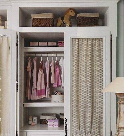 soft gray painted built-in armoire with shirred fabric behind chicken wire doors