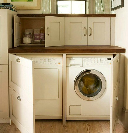 hidden washer and dryer behind cabinet doors from Better Homes and Gardens via Atticmag