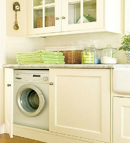 hidden laundry spaces - washer and dryer behind lower cabinet doors from Home Trend Design via Atticmag