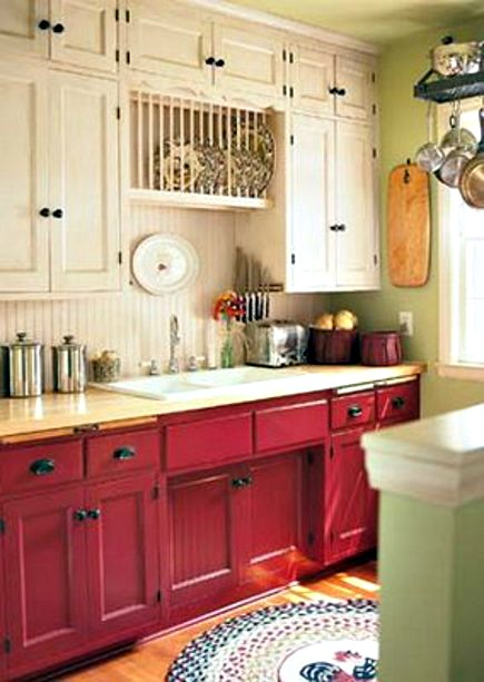 kitchen with red sink base, cream upper cabinets and pale green accent walls