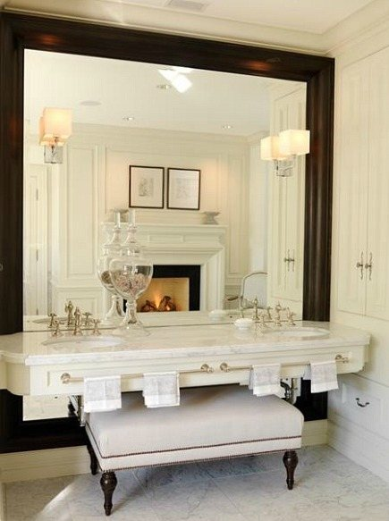 floating vanity is mounted over an oversized wood framed mirror by Julie Charbonneau