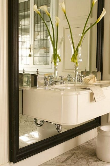 floating vanity mounted over an oversized wood framed mirror by Julie Charbonneau