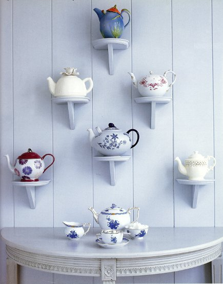 collection of teapots displayed on bracket shelves