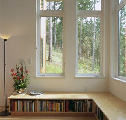 bookcase ideas - corner book case built under picture windows - via Atticmag