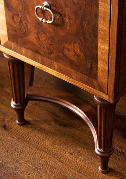 detail of burled walnut and banded mahogany island on legs