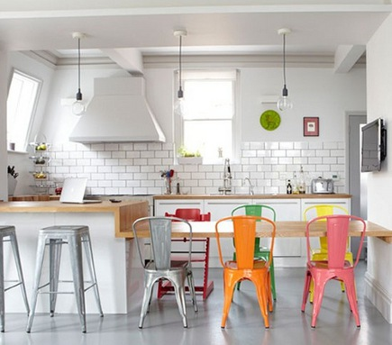 silver, orage, pink and green industrial style chairs at a white kitchen table