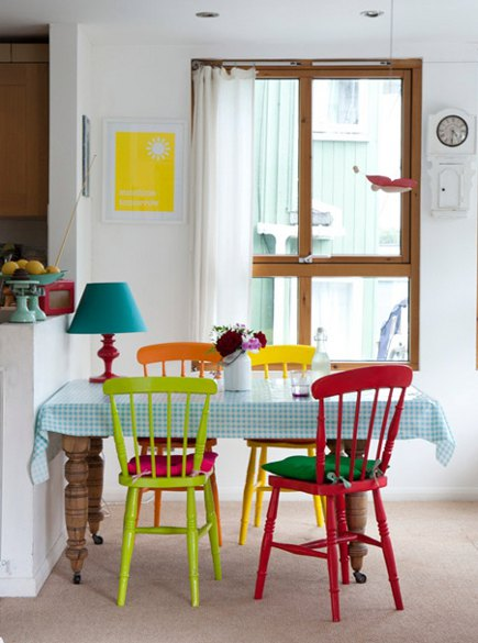 red, green orange and yellow painted chairs at a dining room table