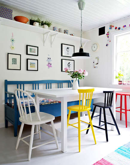 white, yellow and black chairs and a blue bench around a white dining table