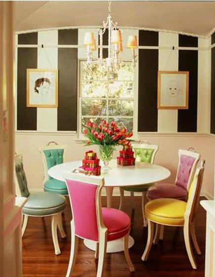 Easter egg color uphostered and tufted chairs around a Saarinen pedestal table