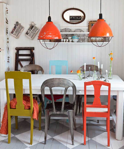 orange, gry, blue and ochre chairs in a cottage dining room
