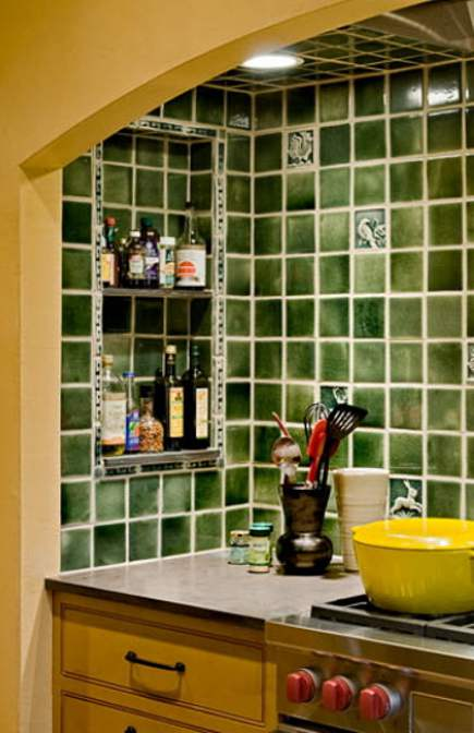details of green Arts & Crafts tile niche in a yellow farmhouse kitchen