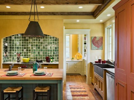 yellow farmhouse kitchen with pine-green tiled range niche