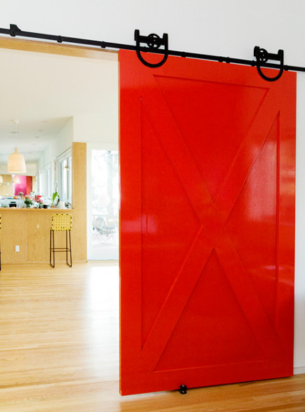 Red lacquer barn door in a home by by Barbara Bestor