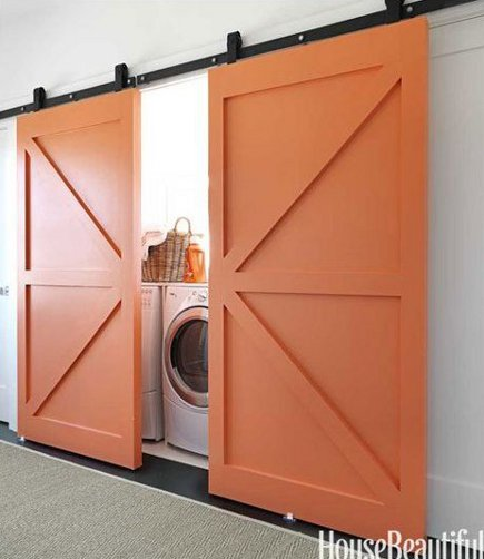 pair of orange barn doors conceal a laundry space
