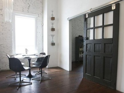 black-painted paneled barn door with six lites